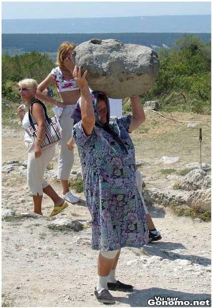 Une vieille femme avec une force herculeenne porte une grosse pierre