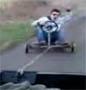 Il fait du kart accroche derriere une voiture. Accident a la fin, Normal !