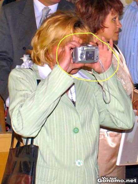 Une blonde derriere l objectif tiens son appareil photo a l envers