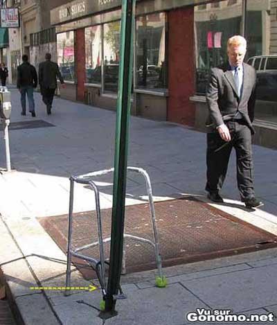 Un dehambulateur attache avec un cadenas a un poteau dans la rue