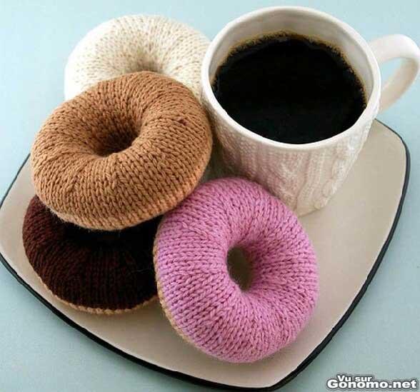 Une bonne tasse de cafe accompagnee de quatres gros donuts en laine a tricoter