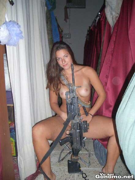 Une fille a poil pose avec un fusil de combat