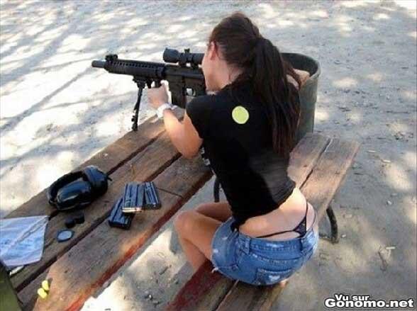 Une belle brune amatrice d armes a feu avec le string qui depasse !