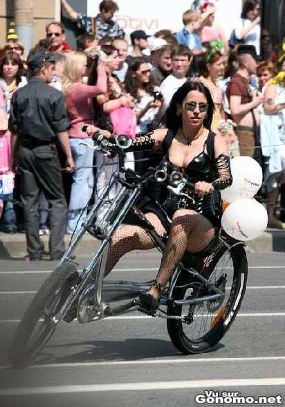 Une bikeuse sexy en cuir sur un velo