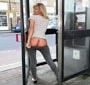 Une charmante blonde montre ses fesses dans une cabine telephonique publique
