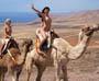 Nu dans le desert : deux filles nues font une balade en dromadaire dans le desert